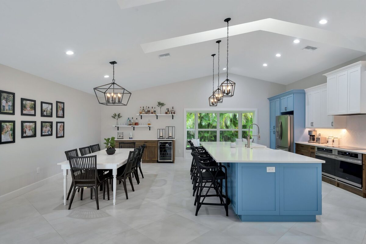View of open concept dining room and modern, remodeled kitchen with bar area and custom window seat.