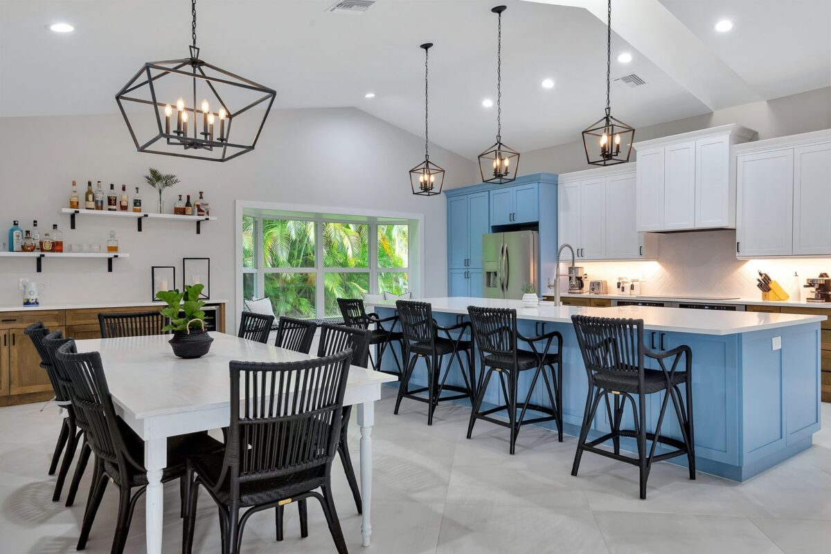 Wide angle shot of full kitchen remodel with ocean blue and white cabinetry and black cage lantern pendant lighting.
