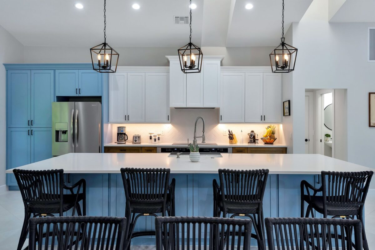 Wide angle shot of coastal kitchen featuring white chevron backsplash, expansive island, and spacious cabinetry.