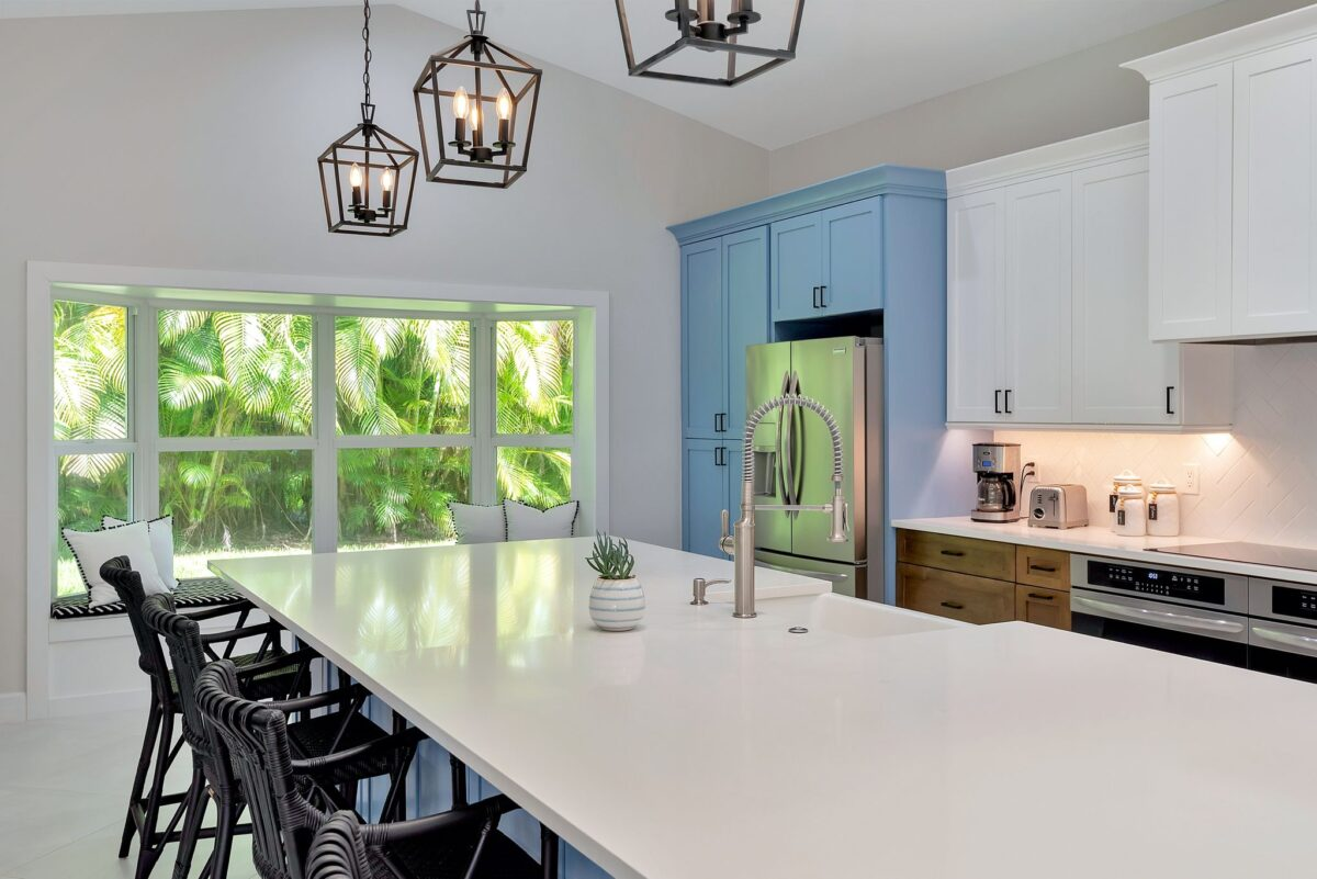Modern kitchen renovation overview with gorgeous palm tree filled window at back and stunning kitchen island centered.