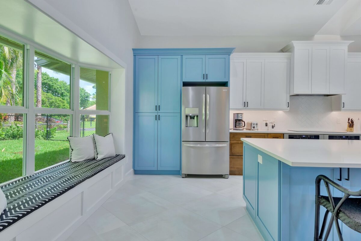 Modern kitchen remodel that features built-in window seat and pops of ocean blue island and cabinets.