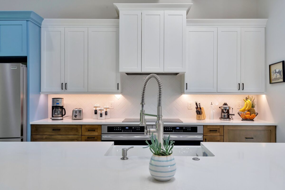 Close up view of large, white quartz kitchen island and large white cabinetry with pop of color blocked ocean blue.