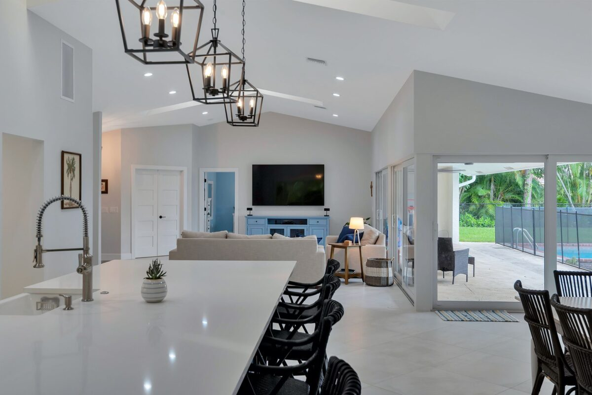 Modern kitchen renovation with tall ceilings and open floor plan between kitchen, dining, and living rooms.