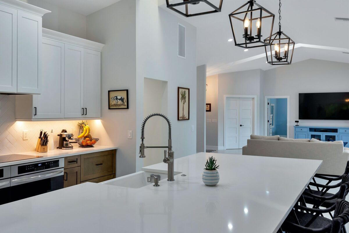 Sparkling white quartz kitchen island countertop featuring stainless steel pull down faucet.
