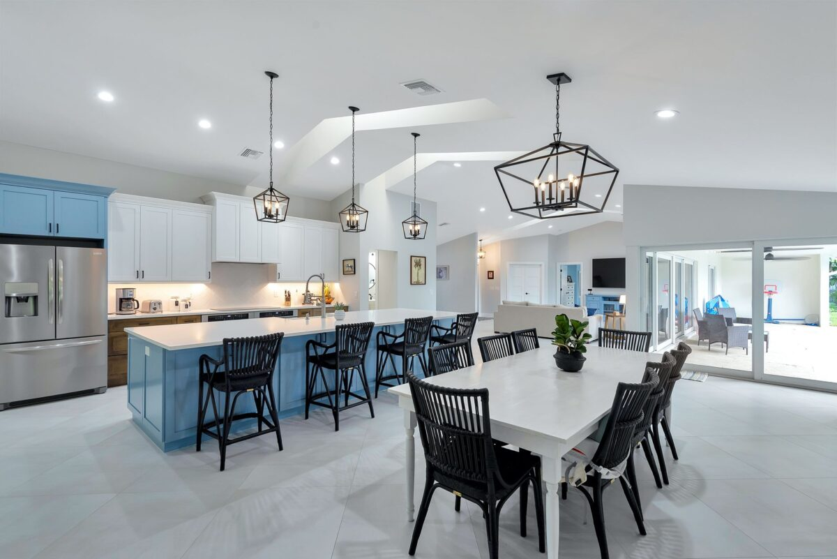 Modern kitchen remodel overview with white dining table and ocean blue kitchen island featuring stainless steel appliances.