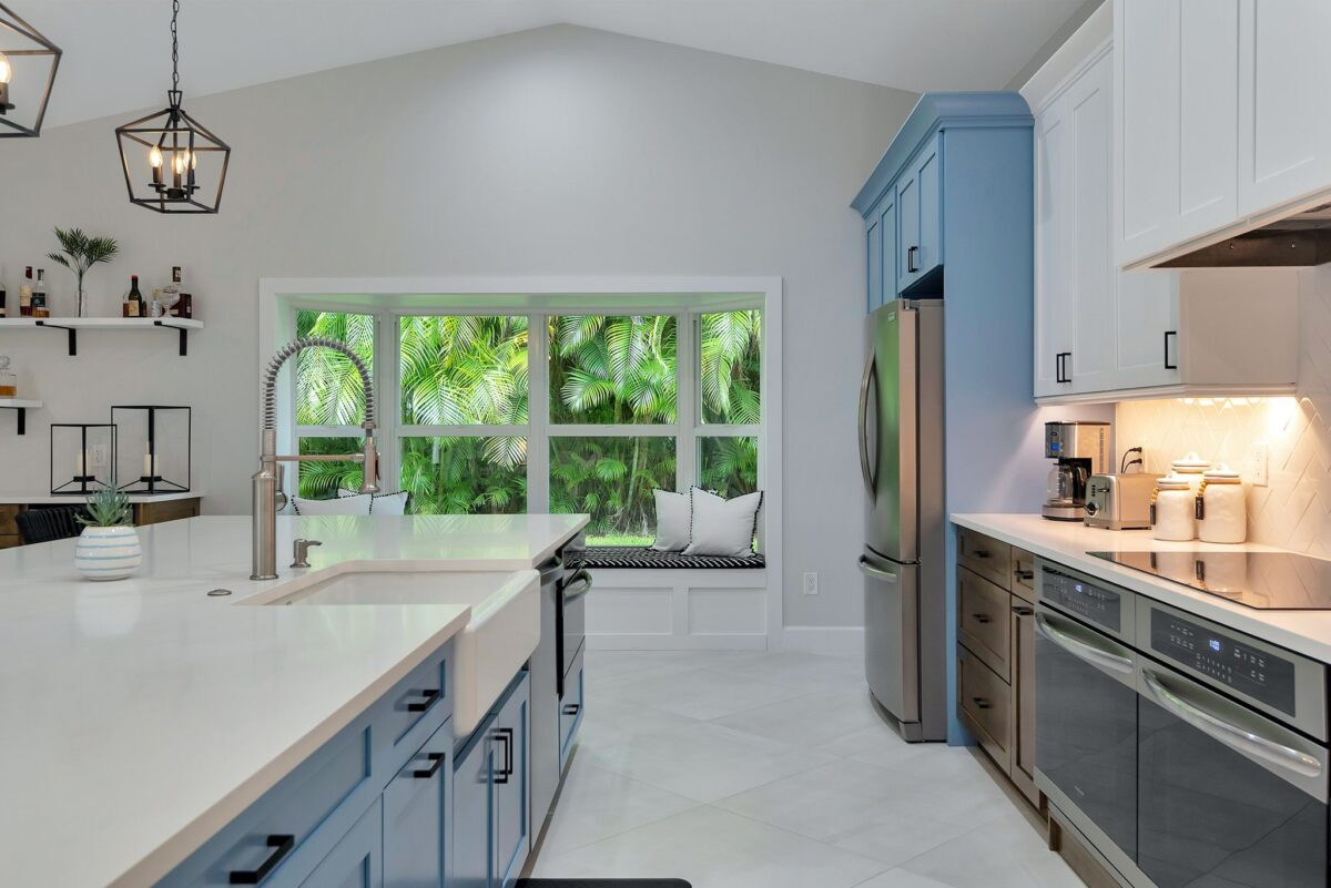 Galley angle of contemporary kitchen remodel looking at board and batten white window seat overlooking window palm tree view.