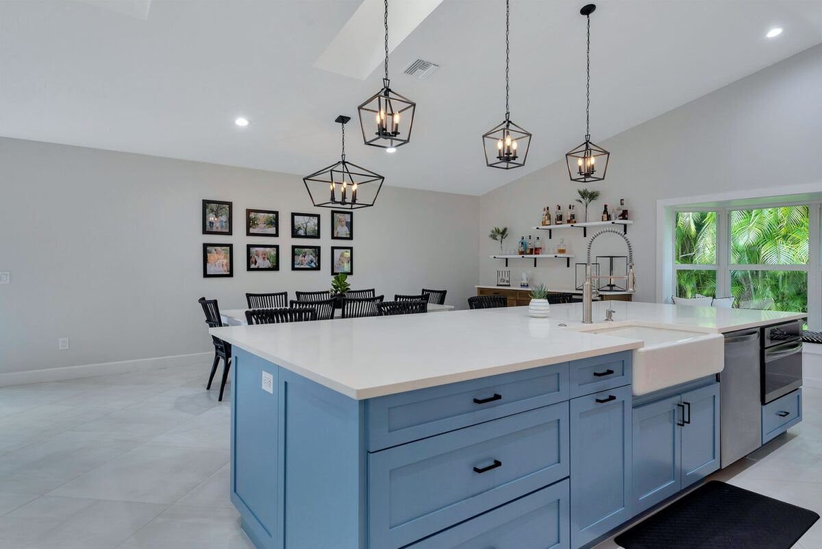 Contemporary, ocean blue colored kitchen island with white quartz countertops and farmhouse sink.
