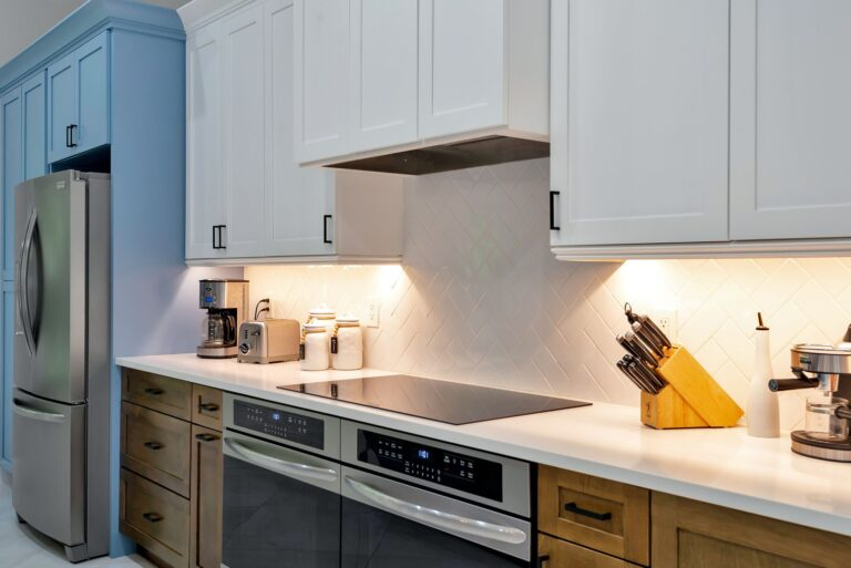View of stainless steel refrigerator and range in modern, coastal style kitchen remodel.