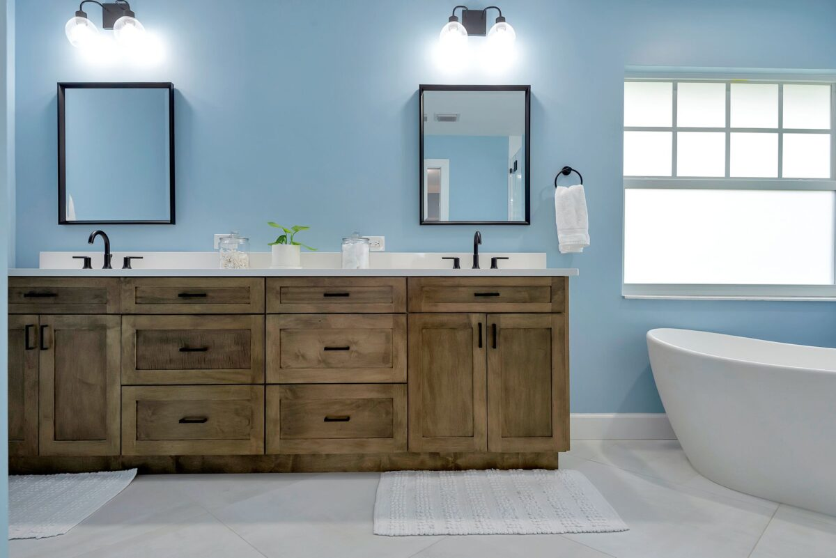 Full contemporary bathroom remodel robust vanity with ample storage, coastal theme with ocean colored walls, black hardware, lighting, and mirror frames.