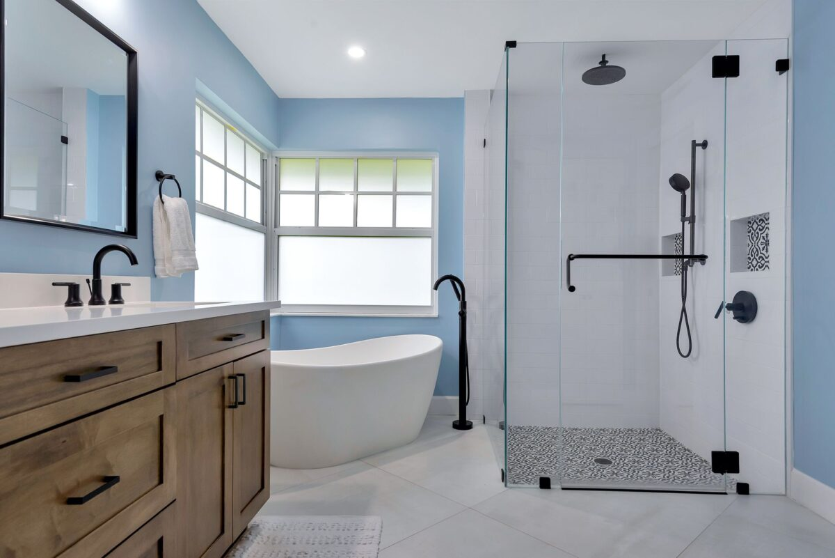 Full bathroom remodel featuring floating tub, his and hers shower with tile floor accents and waterfall shower head.