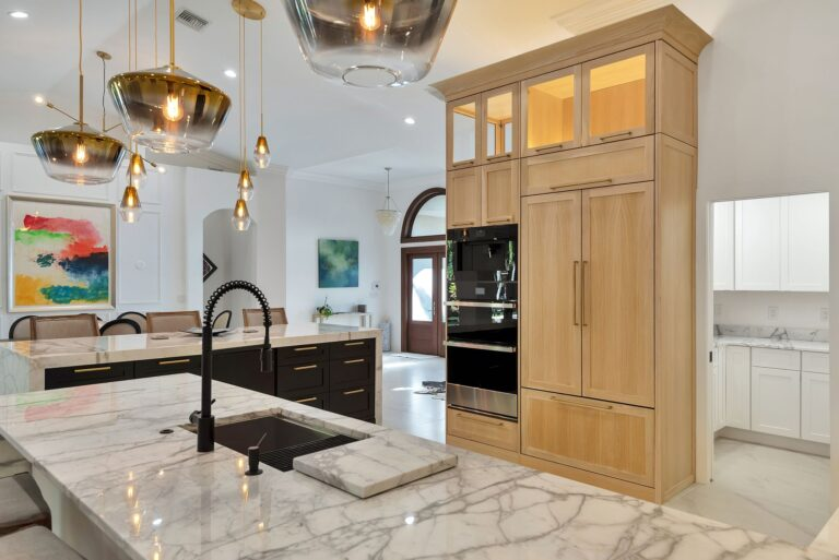 Contemporary remodeled kitchen featuring Carrara marble countertops and gold pendant lighting.