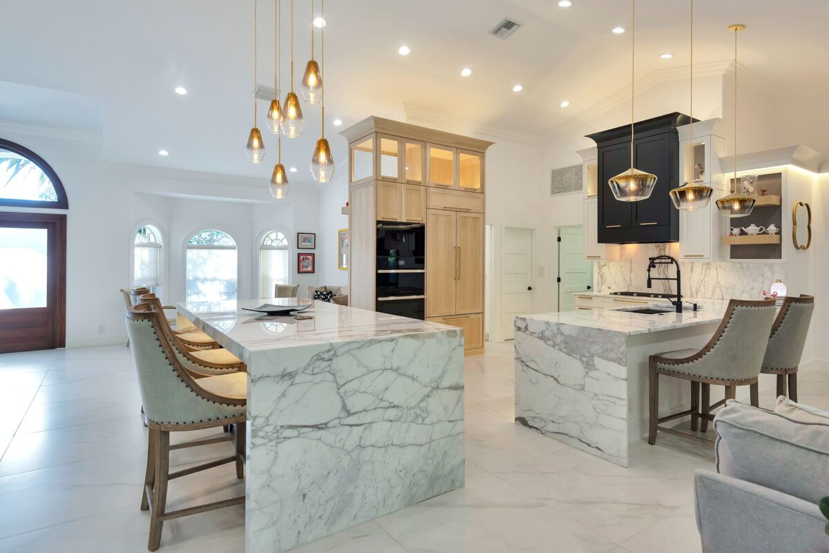 Full modern kitchen remodel featuring polished Carrara marble countertops with waterfall edge, gold accent lighting, large cabinetry display with mixed black and blonde wood.