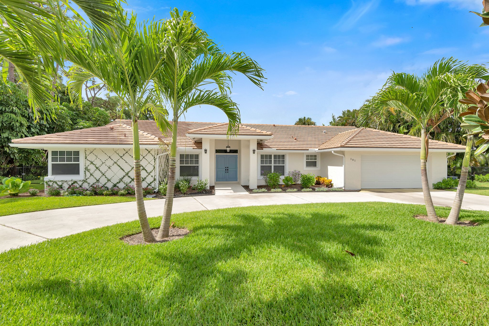 Exterior home remodel featuring brand new impact windows and doors in sunny South Florida.